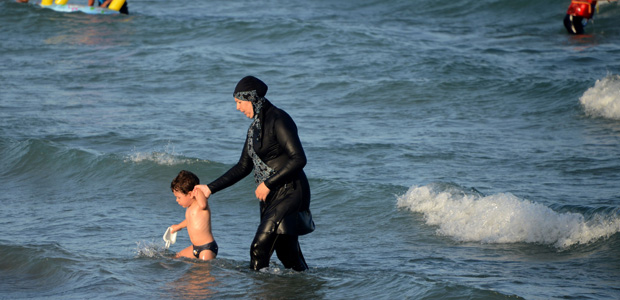 "A Tunisian woman wearing a ""burkini"", a full-body swimsuit designed for Muslim women, walks in the water with a child on August 16, 2016 at Ghar El Melh beach near Bizerte, north-east of the capital Tunis. / AFP PHOTO / FETHI BELAID ORG XMIT: 3058"