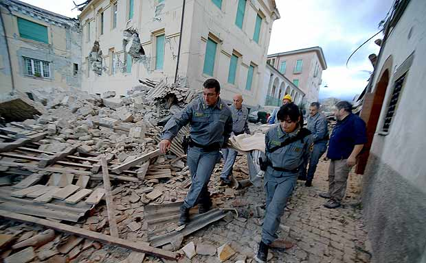 TOPSHOT - Rescuers carry a man from the rubble after a strong heartquake hit Amatrice on August 24, 2016. Central Italy was struck by a powerful, 6.2-magnitude earthquake in the early hours, which has killed at least three people and devastated dozens of mountain villages. Numerous buildings had collapsed in communities close to the epicenter of the quake near the town of Norcia in the region of Umbria, witnesses told Italian media, with an increase in the death toll highly likely. / AFP PHOTO / FILIPPO MONTEFORTE ORG XMIT: ROM062
