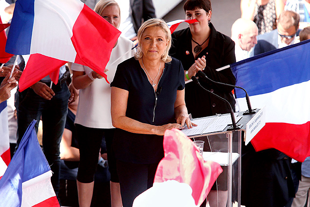 "French far-right party Front National (FN) President and member of the European Parliament, Marine Le Pen looks on as she delivers a speech on September 3, 2016 during a FN political rally in Brachay, northeastern France. Marine Le Pen accused former French president Nicolas Sarkozy to ""allegiance"" to the king Salman of Saudi Arabia ""global promoter of Wahabism"". She also reiterated that she would hold a referendum on the membership of France in the European Union if she is elected President of the Republic in 2017. / AFP PHOTO / FRANCOIS NASCIMBENI ORG XMIT: 164"