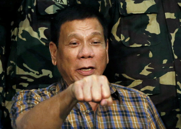 """Philippine President Rodrigo Duterte makes a """"fist bump"""", his May presidential elections campaign gesture, with soldiers during a visit at an army Camp Capinpin military camp in Tanay, Rizal in the Philippines August 24, 2016. REUTERS/Erik De Castro ORG XMIT: GGGEDC905"""