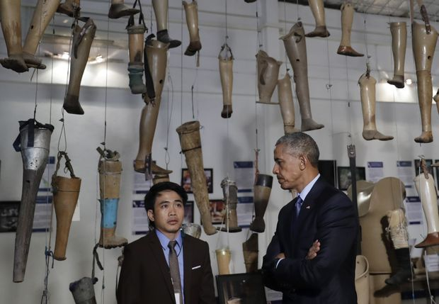 As prostheses hang overhead U.S. President Barack Obama tours the Cooperative Orthotic and Prosthetic Enterprise (COPE) Visitor Centre in Vientiane, Laos, Wednesday, Sept. 7, 2016. (AP Photo/Carolyn Kaster) ORG XMIT: LAOK109