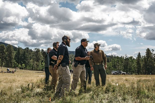 Curtis Simmons, foreground, instructs Samson Smith, with handgun, during an Iron Protection Group training session, outside Bailey, Colo., Aug. 26, 2016. In Colorado, a curious marriage has formed between the booming cannabis industry and its young war veterans, more than 200 of whom of have taken jobs protecting marijuana businesses across the state. (Ryan David Brown/The New York Times)