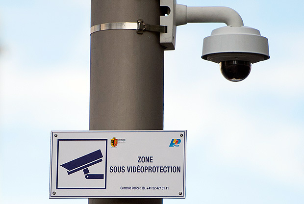 FILE - The Oct. 14, 2014 file photo shows a surveillance camera and a sign indicating the surveillance zone in the neighborhood of Paquis close to the central train station in Geneva, Switzerland. On Sept. 25, 2016 Swiss voters are casting ballots to decide whether to grant new powers to Switzerland's intelligence services, such as tracking internet activity, snooping on email boxes and tapping phones to better fight spies, criminal hackers and violent extremists. (Jean-Christophe Bott/Keystone via AP) ORG XMIT: FOS104