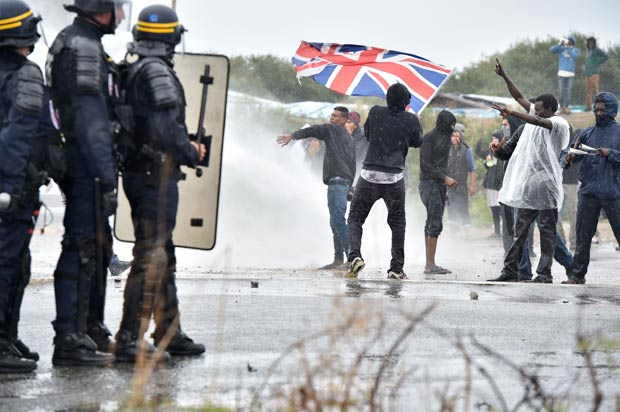 "A participant holds up the Union Jack as French anti-riot police fire water canons at participants during a march organized by human rights activists in support of migrants and refugees in the so-called 'Jungle' camp in the French northern port city of Calais on October 1, 2016. Between 7,000 and 10,000 migrants are currently living in the ""Jungle"", the launchpad for their attempts to stow away on lorries heading across the Channel to England. Rights groups have criticised the hardship and dangers facing the migrants living in the camp, particularly the hundreds of unaccompanied minors. / AFP PHOTO / PHILIPPE HUGUEN"