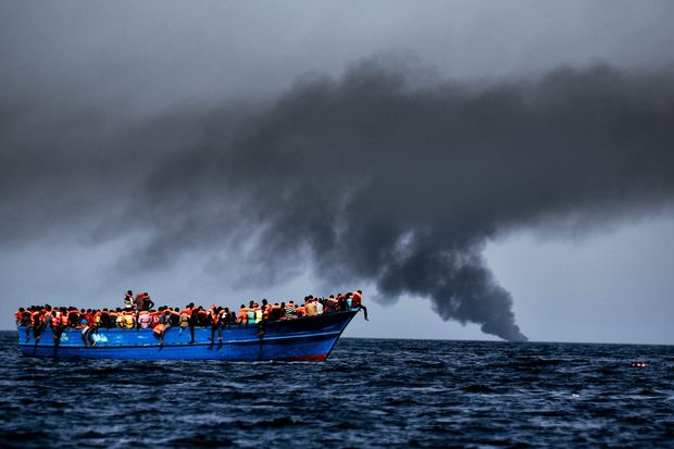 Migrants wait to be rescued as they drift at sunset in the Mediterranean Sea some 20 nautical miles north off the coast of Libya on October 3, 2016. Italy coordinated the rescue of more than 5,600 migrants off Libya, three years to the day after 366 people died in a sinking that first alerted the world to the Mediterranean migrant crisis. / AFP PHOTO / ARIS MESSINIS ORG XMIT: ARIS2438