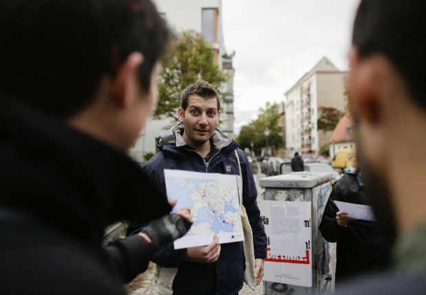 "In this photo taken Sunday, Oct. 9, 2016 refugee Firas Zakri from Syria, a tour guide of the so-called 'Refugee Tours' shows a map of Europe and the Mediterranean Sea as he tours with a group of people through the district of Neukoelln in Berlin, Germany. Zakri is one of four refugee guides with ""querstadtein,"" or ""cross-city,"" a non-profit that initially started off offering tours of Berlin led by formerly homeless people."