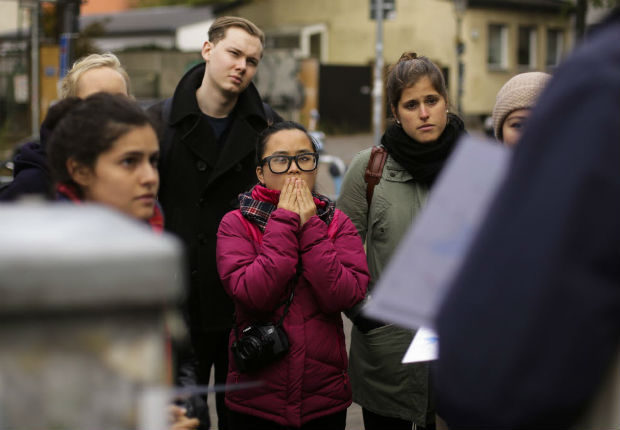 "In this photo taken Sunday, Oct. 9, 2016 people listen to refugee Firas Zakri from Syria, a tour guide of the so-called 'Refugee Tours' as they tour through the district of Neukoelln in Berlin, Germany. Zakri is one of four refugee guides with ""querstadtein,"" or ""cross-city,"" a non-profit that initially started off offering tours of Berlin led by formerly homeless people."