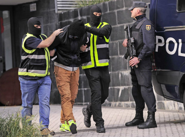 Members of the Spanish National Police escort an arrested man accused of collaborating with the Islamic State in San Sebastian on October 11, 2016. Spanish police have arrested two men on suspicion of seeking recruits for the Islamic State group, the interior ministry said today.