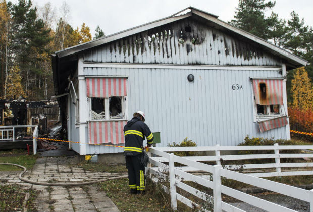 A fireman walks outside a burnt down home for asylum seekers in Sigtuna north of Stockholm, Sweden, Friday, Oct. 21, 2016. Police in Sweden says an asylum center near the capital has burnt down to the ground in the second such incident in a week. Spokeswoman Karina Skagerlind says both blazes are being treating as possible arson by investigators. Skagerlind said nine asylum-seekers and two staff were evacuated as Friday's predawn fire engulfed the building in Sigtuna, north of Stockholm.
