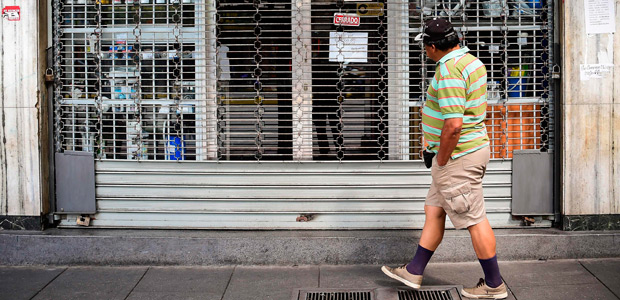 A man passes by a closed store in Caracas, on October 28, 2016. Venezuela's opposition sought to pressure President Nicolas Maduro on Friday with a strike, which he threatened to break with army takeovers of paralyzed firms. The strike risks exacerbating the shortages of food and goods gripping the country, but it seemed to be only partially observed on Friday morning. / AFP PHOTO / RONALDO SCHEMIDT ORG XMIT: RSA690
