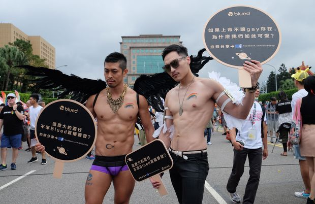 Participants hold up signs during the annual Taiwan lesbian, gay, bisexual and transgender pride parade in Taipei on October 29, 2016. Thousands of the same-sex activists marched in the streets in front of the Presidential Palace in Taipei calling the public to respect marriage equality. / AFP PHOTO / SAM YEH ORG XMIT: SY3699