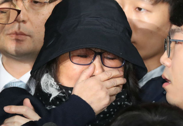 Choi Soon-Sil (C) is surrounded by the media as she arrives at the Seoul Central District Prosecutor's Office in Seoul on October 31, 2016. South Korean prosecutors questioned the woman at the centre of a political scandal that has shattered public confidence in President Park Geun-Hye, with allegations of fraud and meddling in state affairs. / AFP PHOTO / YONHAP / Yonhap / - South Korea OUT / REPUBLIC OF KOREA OUT NO ARCHIVES RESTRICTED TO SUBSCRIPTION USE ORG XMIT: Contact with YONHAPNEWS AGENCY.