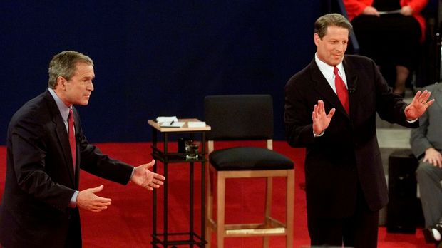 Republican presidential candidate and Texas Governor George W. Bush (L) and Democratic presidential candidate U.S. Vice President Al Gore both gesture toward moderator Jim Lehrer during the town hall-style presidential debate at Washington University in St. Louis, U.S., October 17, 2000. REUTERS/Jeff Mitchell/File Photo ORG XMIT: WAS457