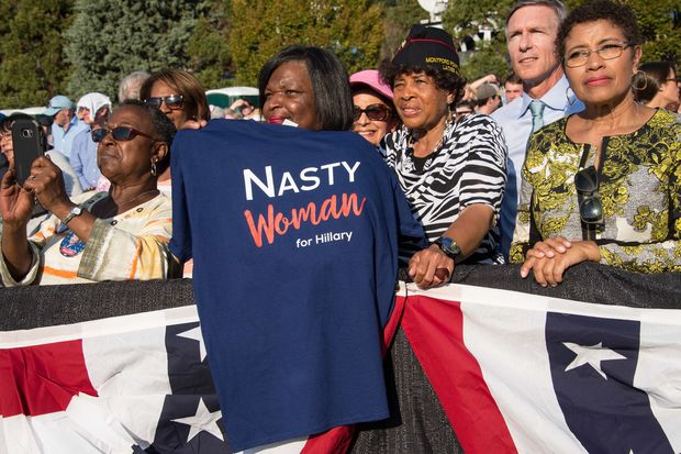 A woman holds a T-shirt as US President Barack Obama speaks at a rally for Democratic presidential candidate Hillary Clinton at the University of North Carolina in Chapel Hill on November 2, 2016. / AFP PHOTO / NICHOLAS KAMM ORG XMIT: NK1159