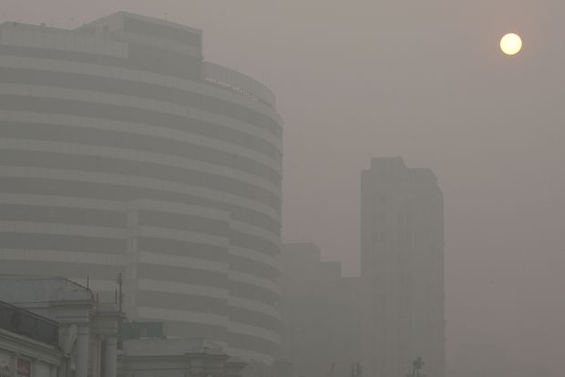 In this photograph taken on November 7, 2016, the sun appears through heavy smog in the Connaught Place area of New Delhi on November 7, 2016. Schools in the Indian capital will be closed for the next three days, the Delhi state goverment said on November 6, as the city struggles with one of the worst spells of air pollution in recent years