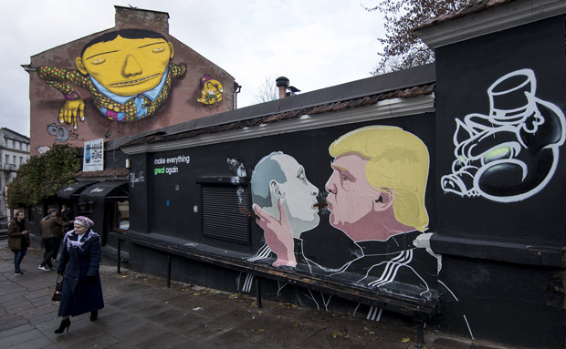 A woman walks past a graffiti artwork depicting Russian President Vladimir Putin, left, and Republican presidential candidate Donald Trump, on the walls of a bar in the old town in Vilnius, Lithuania, Sunday, Oct. 30, 2016. (AP Photo/Mindaugas Kulbis) ORG XMIT: XMK101
