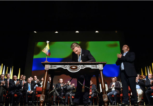 Colombian President Juan Manuel Santos (L) signs the historic peace agreement between the Colombian government and the Revolutionary Armed Forces of Colombia (FARC), at the Colon Theater in Bogota, Colombia, on November 24, 2016. Under pressure for fear that a fragile ceasefire could break down, the government and the Revolutionary Armed Forces of Colombia (FARC) sign the new deal and immediately take it to Congress. The plan bypasses a vote by the Colombian people after they unexpectedly rejected the first version of the deal in a referendum last month. The accord aims to end Latin America's last major armed conflict. But opponents say it is too soft on the leftist FARC force, blamed for many thousands of killings and kidnappings. / AFP PHOTO / Cesar CARRION