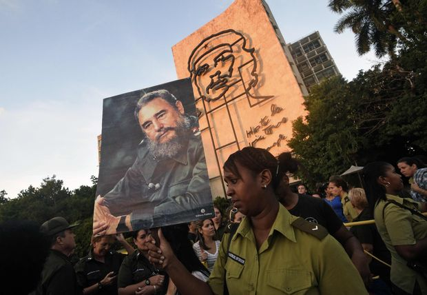 A soldier holds a picture of late Cuban revolutionary leader Fidel Castro as Cubans gather at Revolution Square to pay homage to him, in Havana, on November 29, 2016. A titan of the 20th century who beat the odds to endure into the 21st, Castro died late Friday after surviving 11 US administrations and hundreds of assassination attempts. No cause of death was given. Castro's ashes will go on a four-day island-wide procession starting Wednesday before being buried in the southeastern city of Santiago de Cuba on December 4. / AFP PHOTO / RODRIGO ARANGUA ORG XMIT: RAA1553