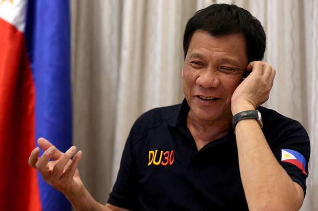 This handout photo taken by the Presidential Photographers' Division on December 2, 2016 and released December 3, 2016 shows Philippines' President Rodrigo Duterte gesturing as he talks to US President-elect Donald Trump on the phone at Legaspi Suites in Davao City. US President-elect Donald Trump told Duterte that Manila was conducting its deadly drug war