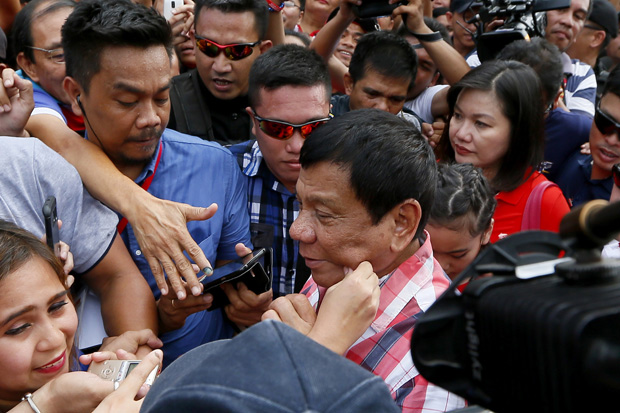 A supporter pinches the cheek of front-running presidential candidate Mayor Rodrigo Duterte as he leaves Daniel R. Aguinaldo National High School at Matina district, his hometown, after voting in Davao city in southern Philippines on May 9, 2016.