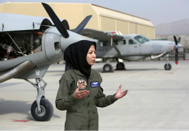 In this Monday, Nov. 21, 2016, photo, Capt. Safia Ferozi, 26, speaks in an interview with the Associated Press after her flight, at the Afghan military airbase in Kabul, Afghanistan. From a childhood as a refugee, Capt. Safia Ferozi is now flying a transport plane for Afghanistan's air force as the country's second female pilot, a sign of the efforts to bring more women into the armed forces. (AP Photo/Rahmat Gul) ORG XMIT: XRG104