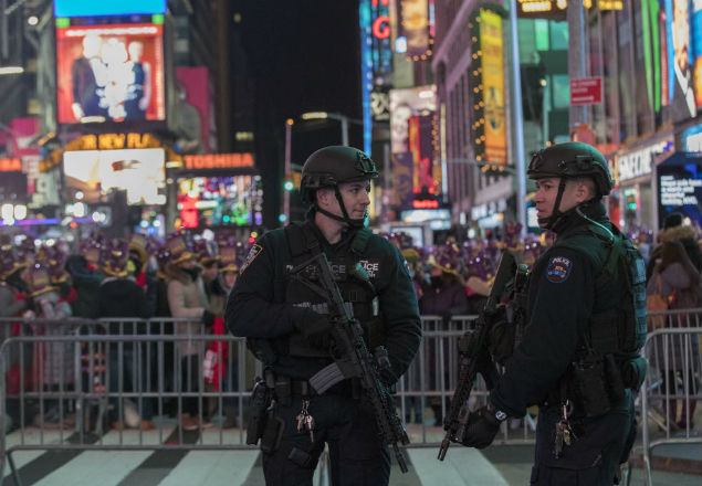 Police officers stand guard as revelers take part in a New Year's Eve celebration in New York's Times Square, Saturday, Dec. 31, 2016. (AP Photo/Mary Altaffer) ORG XMIT: NYMA104