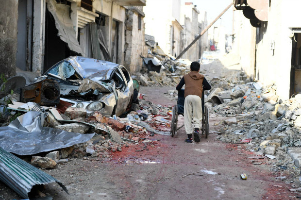 A boy pushes a wheelchair along a damaged street in the east Aleppo neighborhood of al-Mashatiyeh, Syria, in this handout picture provided by UNHCR on January 4, 2017. Bassam Diab/UNHCR/Handout via REUTERS ATTENTION EDITORS - THIS PICTURE WAS PROVIDED BY A THIRD PARTY. REUTERS IS UNABLE TO INDEPENDENTLY VERIFY THE AUTHENTICITY, CONTENT, LOCATION OR DATE OF THIS IMAGE. FOR EDITORIAL USE ONLY. ORG XMIT: SYR05