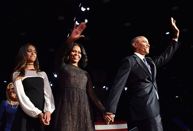 US First Lady Michelle Obama (C) and US President Barack Obama wave to supporters as daughter Malia looks on after the President delivered his farewell address in Chicago, Illinois on January 10, 2017. Barack Obama closes the book on his presidency, with a farewell speech in Chicago that will try to lift supporters shaken by Donald Trump's shock election. / AFP PHOTO / Nicholas Kamm