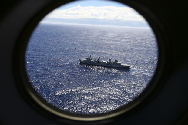 FILE - In this March 31, 2014 file photo, HMAS Success scans the southern Indian Ocean, near the coast of Western Australia, as a Royal New Zealand Air Force P3 Orion flies over, while searching for missing Malaysia Airlines Flight MH370. After nearly three years, the hunt for Malaysia Airlines Flight 370 ended in futility and frustration on Tuesday, Jan. 17, 2017, as crews completed their deep-sea search of a desolate stretch of the Indian Ocean without finding a single trace of the plane.