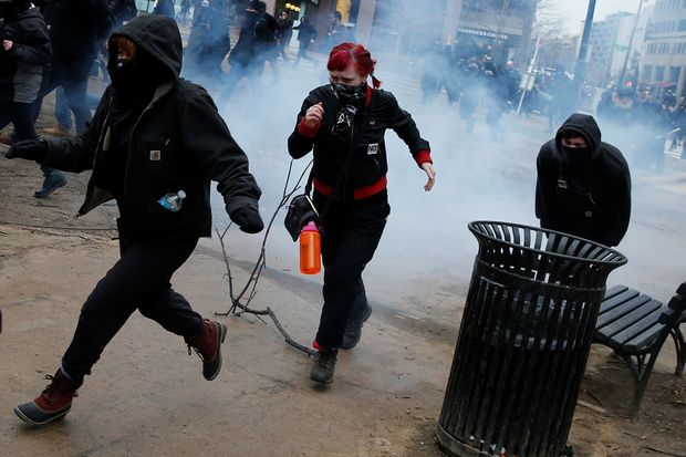 Activists run after being hit by a stun grenade while protesting against U.S. President Donald Trump on the sidelines of the inauguration in Washington, DC, U.S., January 20, 2017.