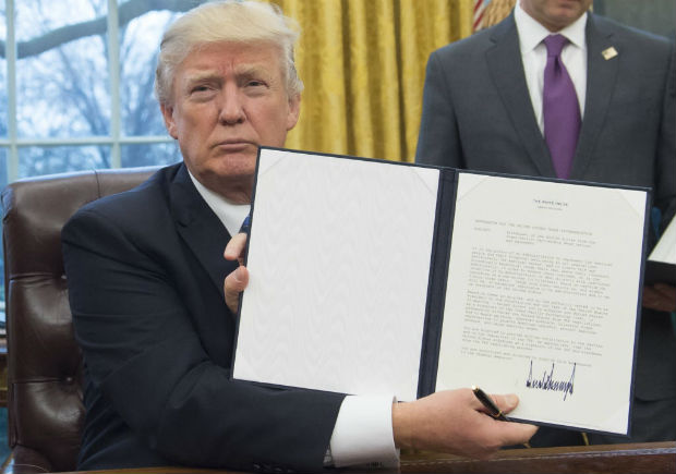 TOPSHOT - US President Donald Trump holds up an executive order withdrawing the US from the Trans-Pacific Partnership after signing it in the Oval Office of the White House in Washington, DC, January 23, 2017. Trump the decree Monday that effectively ends US participation in a sweeping trans-Pacific free trade agreement negotiated under former president Barack Obama. / AFP PHOTO / SAUL LOEB ORG XMIT: SAL001