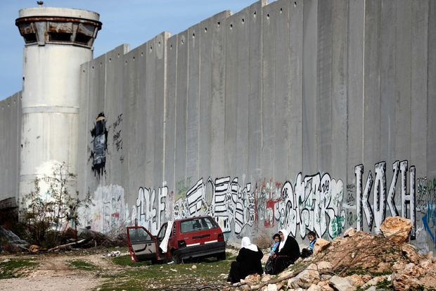Palestinian women and girls sit in front of Israel's controversial separation barrier between the West Bank city of Bethlehem and Jerusalem on January 17, 2017.