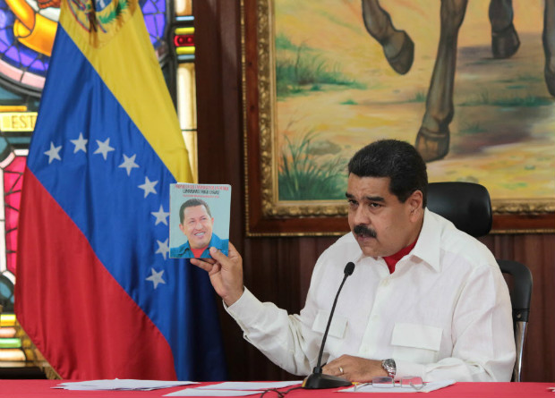 Venezuela's President Nicolas Maduro holds an image of Venezuela's late President Hugo Chavez as he speaks during a meeting with governors in Caracas, Venezuela February 14, 2017. Miraflores Palace/Handout via REUTERS ATTENTION EDITORS - THIS PICTURE WAS PROVIDED BY A THIRD PARTY. EDITORIAL USE ONLY. ORG XMIT: VEN05