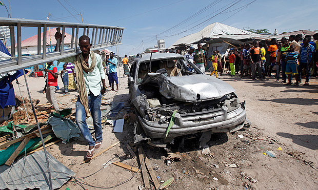 A man walks past a wrecked vehicle after a blast in a market in the capital Mogadishu, Somalia Sunday, Feb. 19, 2017. A Somali police officer says a blast at a busy market in the western part of Somalia's capital tore through shops and food stands and killed more than a dozen people and wounded many others. (AP Photo/Farah Abdi Warsameh) ORG XMIT: NAI104