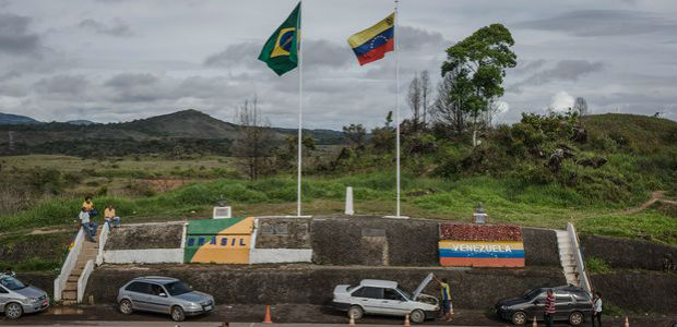 Venezuelans walk across the border from Venezuela into the Brazilian city of Pacaraima, Roraima state
