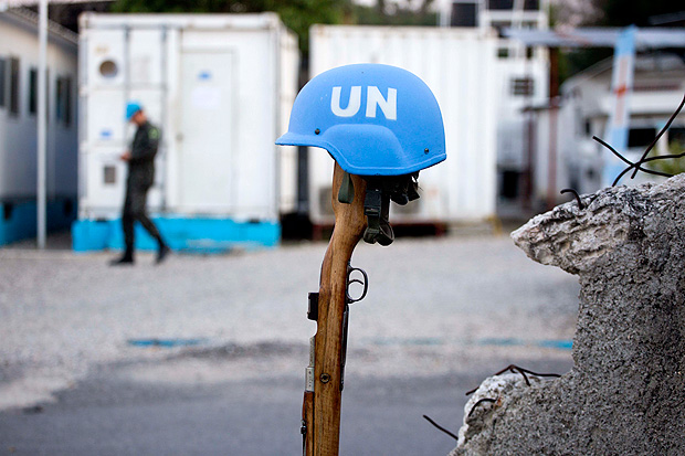 """This Feb. 22, 2017 photo shows a U.N. peacekeeper's blue helmet balanced on a weapon in Port-au-Prince, Haiti. """"We have a secure and stable environment,"""" said Col. Luis Antonio Ferreira Marques Ramos, deputy commander of the Brazilian peacekeeper contingent in Haiti. """"The important thing is to leave in a good way."""" (AP Photo/Dieu Nalio Chery) ORG XMIT: DC312"""