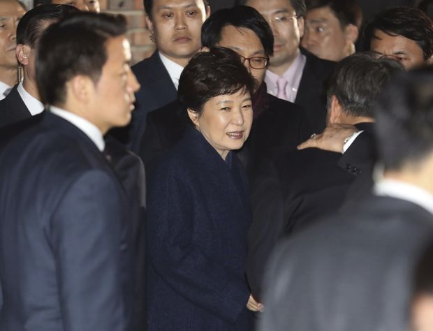Ousted South Korea's former President Park Geun-hye, center, arrives at her private home in Seoul, South Korea, Sunday, March 12, 2017. Park on Sunday expressed defiance toward the corruption allegations against her as she vacated the presidential palace and returned to her home two days after the Constitutional Court removed her from office. (Choi Jae-koo/Yonhap via AP) ORG XMIT: XSEL801