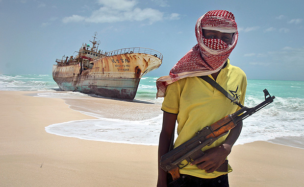FILE - In this Sunday, Sept. 23, 2012 file photo, masked and armed Somali pirate Hassan stands near a Taiwanese fishing vessel washed ashore after the pirates were paid a ransom and the crew were released in the once-bustling pirate den of Hobyo, Somalia. Pirates have hijacked an oil tanker off the coast of Somalia, Somali officials and piracy experts said Tuesday, March 14, 2017, in the first hijacking of a large commercial vessel there since 2012. (AP Photo/Farah Abdi Warsameh, File) ORG XMIT: NAI105