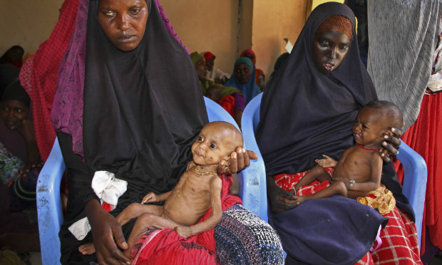In this photo taken Saturday, Feb. 25, 2017, malnourished baby Ali Hassan, 9-months-old, left, is held by his mother Fadumo Abdi Ibrahim, as mother Habiba Mohamed Aden holds her baby Mohamud Ahmed, 6-months-old, right, all of whom fled the drought in southern Somalia, at a feeding center in a camp in Mogadishu, Somalia. Thousands of desperate people are streaming into Somalia's capital seeking food as a result a prolonged drought, overwhelming local and international aid agencies, while the Somali government warns of a looming famine, compounded by the country's ongoing conflict against Islamic extremists. (AP Photo/Farah Abdi Warsameh) ORG XMIT: NAI105