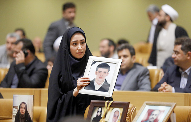 "An Iranian donor holds a portrait during an annual ceremony in Tehran on March 14, 2017, in which charitable donors pay off the debts of mehrieh prisoners as a show of Islamic charity. The ""Mehrieh"" (""affection"") system, in which future husbands agree to pay a certain number of gold coins to the bride in the event of divorce, has left thousands of men in Iran languishing in jail and many more destitute. / AFP PHOTO / ATTA KENARE ORG XMIT: AK274"