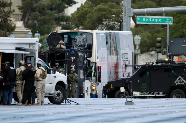 Las Vegas SWAT officers surround a bus along Las Vegas Boulevard, Saturday, March 25, 2017, in Las Vegas. Las Vegas police said the gunman in a fatal shooting on the Strip who barricaded himself inside the public bus has surrendered peacefully after shutting down the busy tourism corridor for hours. (AP Photo/John Locher) ORG XMIT: NVJL105