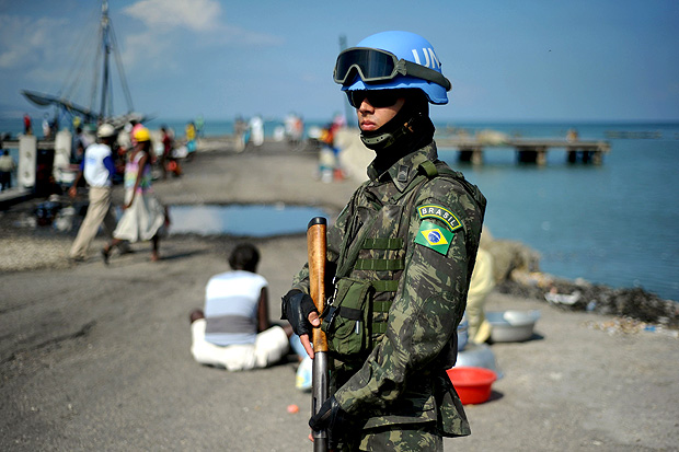 (FILES) This file photo taken on March 11, 2014 shows a Brazilian soldier of the MINUSTAH (United Nations Stabilization Mission in Haiti) peacekeeping contingent patroling in the Cite Soleil slum of Port-au-Prince. The United Nations Security Council on Thursday agreed to shut down the peacekeeping mission in Haiti after 13 years and replace it with a smaller police-only force. / AFP PHOTO / HECTOR RETAMAL ORG XMIT: HR181