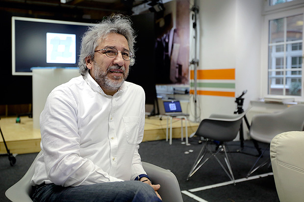 In this April 7, 2017 photo, Can Dundar the former chief editor of the Turkish newspaper Cumhuriyet and now chief editor of the German-Turkish journalistic platform and website 'Ozguruz', which can be translated as 'We Are Free', poses for a photo prior to an interview with the Associated Press in Berlin. In the background the logo of Ozguruz. (AP Photo/Markus Schreiber) ORG XMIT: MSC504
