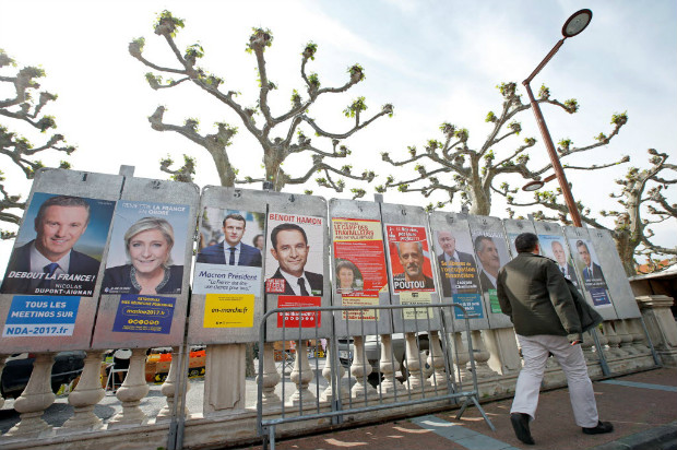 """A man walks past campaign posters of the 11 candidates who run in the 2017 French presidential election in Le Soler, near Perpignan, France April 15, 2017. (L-R) Debout La France group candidate Nicolas Dupont-Aignan, French National Front (FN) political party leader Marine Le Pen, head of the political movement En Marche! (Onwards!) Emmanuel Macron, French Socialist party candidate Benoit Hamon, France's extreme-left Lutte Ouvriere political party (LO) leader Nathalie Arthaud, Anti-Capitalist Party (NPA) presidential candidate Philippe Poutou, """"Solidarite et Progres"""" (Solidarity and Progress) party candidate Jacques Cheminade, lawmaker and independent candidate Jean Lassalle, candidate of the French far-left Parti de Gauche Jean-Luc Melenchon, UPR candidate Francois Asselineau and the Republicans political party candidate Francois Fillon. REUTERS/Jean-Paul Pelissier ORG XMIT: JPP02"""