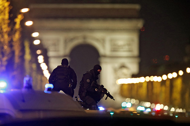 REFILE - CORRECTING CASUALTY NUMBER Masked police stand on top of their vehicle on the Champs Elysees Avenue after a policemen was killed and two others were wounded in a shooting incident in Paris, France, April 20, 2017. REUTERS/Christian Hartmann TPX IMAGES OF THE DAY ORG XMIT: PAR129