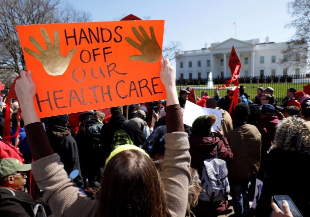 FILE PHOTO: Protesters demonstrate against U.S. President Donald Trump and his plans to end Obamacare outside the White House in Washington, U.S., March 23, 2017. REUTERS/Kevin Lamarque/File Photo ORG XMIT: TOR245