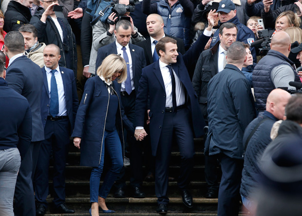 French independent centrist presidential candidate, Emmanuel Macron and his wife Brigitte are greeted by supporters after casting his vote in Le Touquet, France, Sunday, May 7, 2017. Voters across France are choosing a new president in an unusually tense and important election that could decide Europe's future, making a stark choice between pro-business progressive Emmanuel Macron and far-right populist Marine Le Pen. (AP Photo/Thibault Camus) ORG XMIT: TH153