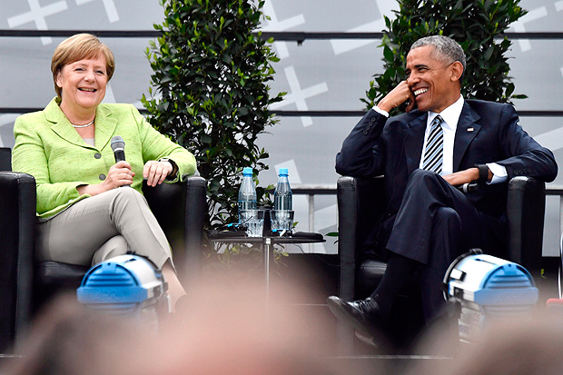 Former US president Barack Obama and Chancellor Angela Merkel laugh as they attend a panel discussion on stage during the Protestant church day (Kirchentag) event at the Brandenburg Gate (Brandenburger Tor) in Berlin on May 25, 2017.?Barack Obama attends a panel dicussion with Angela Merkel in Berlin before heading to Baden-Baden to receive a German media prize. / AFP PHOTO / John MACDOUGALL