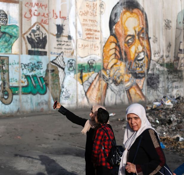 """Palestinian women pose for a """"selfie"""" photograph with a cell phone as they wait in queue by a mural of Fatah leader Marwan Barghuti, painted on a section of Israel's controversial separation wall, next to Qalandia checkpoint in the occupied West Bank on June 9, 2017, in order to attend the second Friday prayers of the Muslim holy month of Ramadan at al-Aqsa mosque in Jerusalem. / AFP PHOTO / ABBAS MOMANI ORG XMIT: AM1644"""