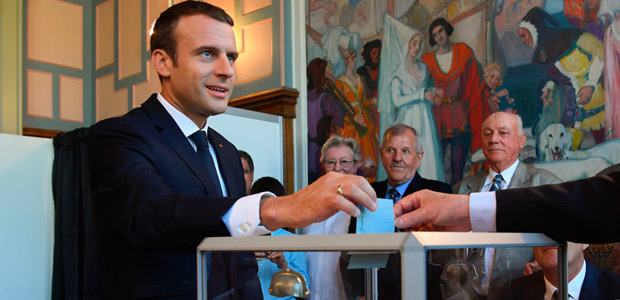 French President Emmanuel Macron casts his ballot as he votes at a polling station in Le Touquet, northern France, during the second round of the French parliamentary elections (elections legislatives in French), on June 18, 2017. / AFP PHOTO / POOL AND AFP PHOTO / CHRISTOPHE ARCHAMBAULT